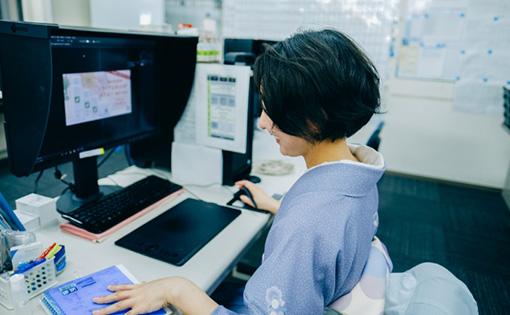 PCに向かって仕事をしている女性の写真